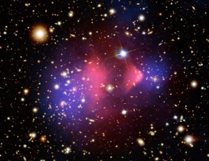 The Bullet Cluster is a galaxy cluster in the process of merging. The pink regions are the hot gas as imaged using X-rays; the blue is the dark matter as found using gravitational lensing. [Credits:  X-ray: NASA/CXC/CfA/ M.Markevitch et al.;Lensing Map: NASA/STScI; ESO WFI; Magellan/U.Arizona/ D.Clowe et al. Optical: NASA/STScI; Magellan/U.Arizona/D.Clowe et al.]