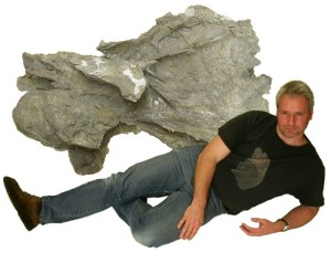 A piece of a Supersaurus vertebra, with paleontologist glamor for reference. While no other part of Supersaurus has been found yet, the shape of the bone identifies it as a sauropod, and the size of the fragment (that's not the whole vertebra!) marks it probably as the largest land animal that ever lived. [Credit: Sauropod Vertebra Picture of the Week/Mike Taylor]