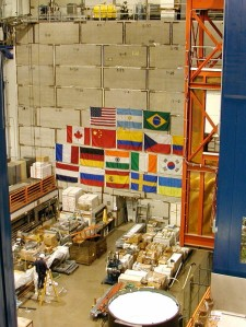 The high bay of the DZero detector at Fermilab. The detector itself lies behind the concrete wall covered in the flags of the 18 nations participating in the project. [Credit: moi]